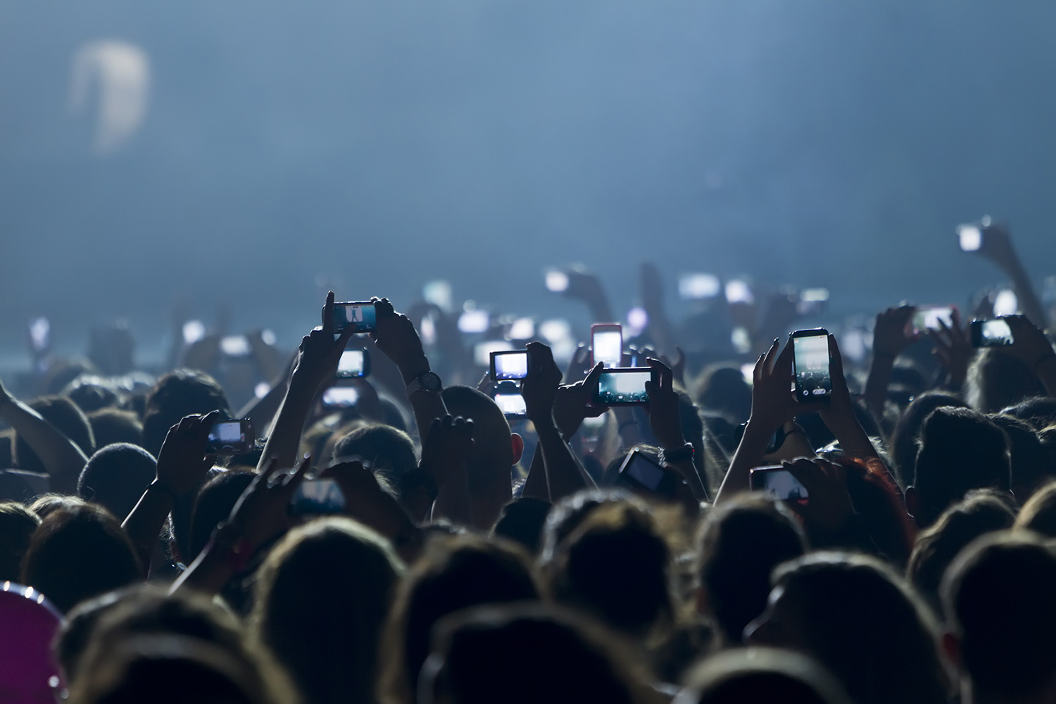 People with phones in the air at a concert